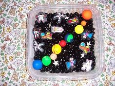 Space sensory bin (the planets are made out of fimo clay) - like the black marble idea for smooth, cool sensory, but maybe bouncy balls for the planets