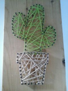 Een cactus in een pot met spijkers en wol gemaakt