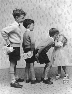 Little Susan Burton exchanges a kiss for a present from each of her brothers on her second birthday (1956)