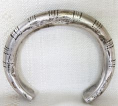 This 19th century hill tribe bracelet is most likely Hmong, or possibly Mien (Yao) in origin since this design was popular with both hill tribe groups. Time and use has created a pleasantly smooth surface with partial erosion of the original etched designs. These heirloom pieces of silver jewellery were passed down through the generations as was custom amongst hill tribe peoples.