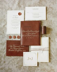 Traditional letterpress invitations are slipped into hand-stitched antique leather envelopes for mailing.