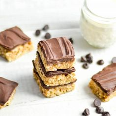 Overhead view of a stack of three No-Bake Chocolate Peanut Butter Coconut Bars with three others around them and a glass of milk in the background