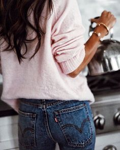 Soft pink oversized sweater with blue jeans.