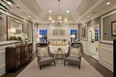Transitional Master Bedroom with High ceiling, Carpet, Hardwood floors, Wainscoting, Crown molding, Chandelier