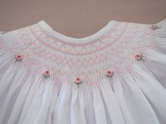 This sweet hand smocked and hand embroidered dress truly is precious. Made of soft white cotton fabric with delicate pink smocking and beautiful rose embroidery adorning the round yoke. Delicate lace trims the short puffy smocked sleeves and hem. And a shadow work bow with long trailing tails and roses decorates the front hem. Closes in the back with delicate white buttons. Lots of time and care went into all the details of this adorable dress, making it an irresistible addition to any…