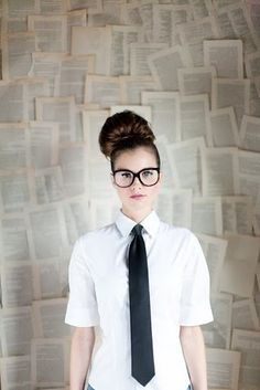 Girl wearing a tie in front of pages of a book