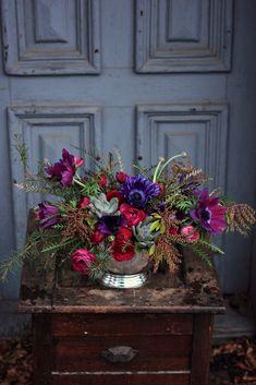 Winter arrangement of anemones, ranunculus, succulents and evergreens. I love everything about this, from the flowers to the silver cachepot to the the shabby wedgewood door..everything!