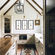 White, warm medium tone wood, steel frame windows, lantern pendant, butcher block island