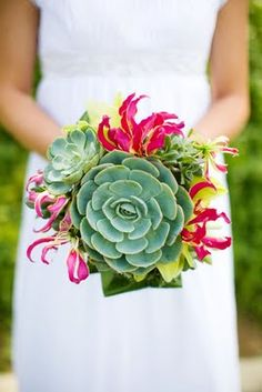 Succulents, gloriosa lily, aspidistra leaves and something yellow in the background that I can't quite tell what it is.  [Bouquet: Aubrey Messick, Photo: Mike Cunningham]