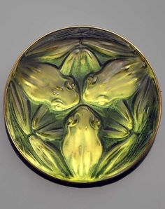 René Lalique - An Art Deco 'Frog' brooch. Molded green glass on reflective background depicting three frogs, mounted in gold. Signed to pin. Model made in 1911. Diameter: 4.3cm