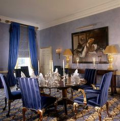 John Stefanidis: Herefordshire, England: The blue, yellow and black rug was made for the room to a design inspired by Emilio Terry.  The parcel-gilt chairs, also made for the room, are covered in a wide satin stripe in Saxon blue.  The intense blue silk curtains hang on poles with neo-classical finials. Beneath them are folding Roman blinds of yellow and blue horsehair. The cornflower blue walls are stippled and below the dado rail are marbled pale blue panels framed in cobalt.