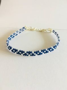 Fun bead loom bracelet in cobalt blue and white colors. This beautiful bracelet is made with delica beads and finished with silver ribbon clasps and a two inch extended chain. Can be worn alone or stacked with other bracelets. If you need something larger or smaller or would like this