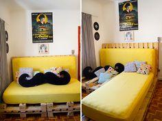 A intenção era comprar um móvel convencional, mas não encontrava um modelo amarelo como queria. Então a solução era fabricar por conta própria: dois paletes apoiados na parede funcionam como encontros. Na base, quatro paletes ficam no chão, com dobradiças, cuja articulação permite que, dobrados, forme o sofá, e esticados virem a cama.