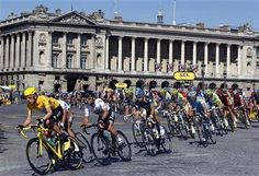 Sky Procycling rider and leader's yellow jersey Bradley Wiggins of Britain (L) cycles on the Place de la Concorde in Paris during the final 20th stage of the 99th Tour de France cycling race