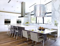 Table extension. Merge your island with your kitchen table for a seamless and functional focal point. The extended island-table combo in this eat-in kitchen isn't short on seating. The thick square table base and low-to-the-ground chairs pay homage to midcentury furniture pieces.