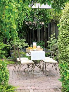 "Dining outdoors is irresistible with a spot as cool as this. ""Silver Sheen"" hedges define the outdoor dining/work space, and wisteria vines cover the arbor. Though it doesn't look like it, the understated dining set came from a garage sale and the chic chandelier came from Ikea."