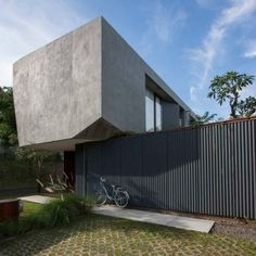 Indonesian house by SUB features  chiselled edges and a grassy courtyard