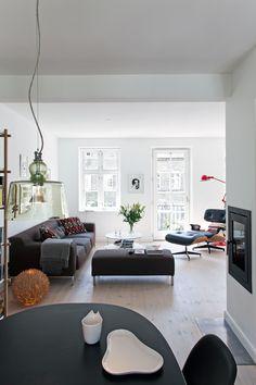 Rummet domineres af en enkel Greg-sofa med puf og et rundt Giro-sofabord – begge fra Zanotta. Eames-lounge- stolen med skammel og gulvlampen i træspån (tv.). Den røde lampe er fra Jielde. I forgrunden spisepladsen med et Piet Hein-bord med sort laminat, som oplyses af en Aquatinta-lampe fra Produzione Privata.