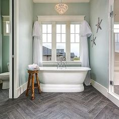 Clark and Co Homes - bathrooms - blue green walls, blue green wall color, herringbone tiled floor, tile that looks like wood, wood effect floor tile, pedestal tub, pedestal bathtub, rustic tripod stool, rustic wooden stool, water closet,
