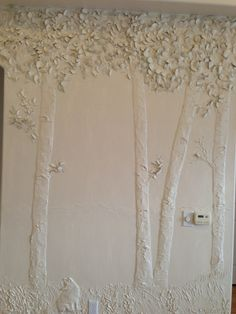 bas relief made out of plaster/compound depicting mountain landscape, aspen trees, mountains and a fox sculpted on the wall