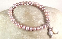 Armband PERLENZAUBER - Echte Perlen sind immer elegant. Die 5-6mm großen Barockperlen dieses Armbands werden ergänzt von zwei kleinen Anhängern.