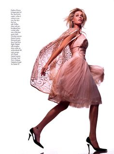 """Rebecca Romijn in a pleated strapless dress and embroidered coat from the Spring 2002 collection. Elle US April 2002 """"Party Girl"""", photographed by Gilles Bensimon"""