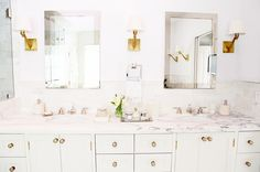 Bathroom with marble tabletops, white cabinets, white walls, large mirrors, and white and gold light fixtures