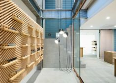 Handmade knifes are displayed on a custom-built wooden shelving system inside this shop for Japanese brand Tadafusa