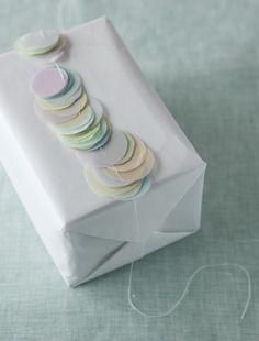 カラフルな薄紙を円形に切って糸でつないだガーランドを巻いて、かわいくラッピング。/おいしいスイーツギフト(「はんど&はあと」2011年9月号)