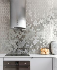 Silver-Tiled Backsplash A silver backsplash is a trendy spin on stainless steel in the kitchen.