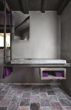 Bathroom design inspiration. Stone flooring and cement sink with wood storage beneath. Unique and beautiful bathroom design.