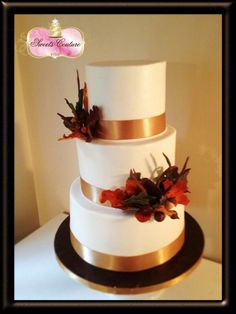 Fall wedding cake with blue ribbon instead of gold and flowers to match the bouquets.