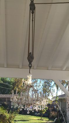 I used a old pulley I bought from a garage sale to hang the thrift store chandelier in the patio