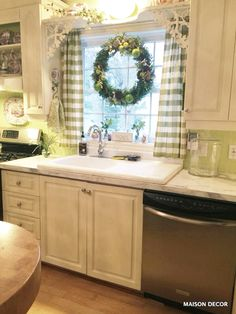 Apple green accents like hand towels in a cute pattern spread the love around an all white kitchen. Sponsored by HomeGoods.