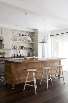 For easy portability, this unique kitchen island on rollers has casters built into its legs allowing for extraordinary utility and dynamic placement. The stunning white barstools make for a very sharp, modern appearance in the kitchen