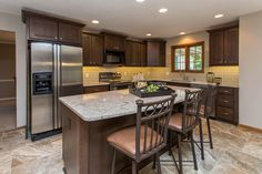 This kitchen was given a new look with maple cabinets, quartz counters, a glass backsplash and an island that can seat the family.