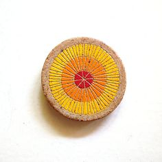 • Ceramic magnet • Approximately 2.75 diameter • Soldate clay • Hand painted with under glazes and then carved with lines