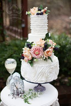Beautiful wedding cake with sculpted frosting, fresh flowers, and blackberries #summerwedding #weddingcake