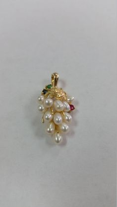 This beautiful grape drop pendant has 12 pearls with one round ruby,sapphire and emerald set in solid 14k yellow gold. The bail on this pendant