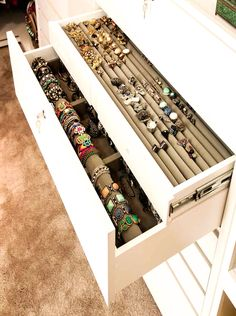 Walk-n closet features built-in jewelry drawers filled with rings and bracelets.