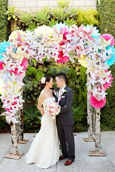 Wedding Canopy & Arches - Create a work of art like this playful wedding arch idea! Decorate a plain wooden altar with colourful pinwheels, lanterns, cut-out decorations, pinwheels, and some more pinwheels.. what fun!  #Wedding #Altar #WeddingCanopy  #WeddingArch #Ceremony