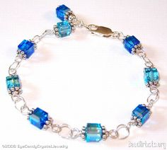 Wire wrapped links bracelet Swarovski crystal cubes wire linked with sterling wire and rings. Sapphire and aqua cubes, Bali daisy spacers. Wear it as is or add your own charms to the rings!