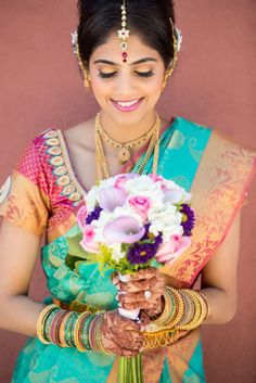 South Indian bride. Temple jewelry. Jhumkis.Teal blue silk kanchipuram sari with contrast pink embroidered blouse.Braid with fresh jasmine flowers. Tamil bride. Telugu bride. Kannada bride. Hindu bride. Malayalee bride.Kerala bride.South Indian wedding.