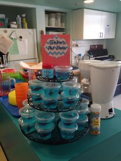 """Mini jello aquariums. Blue jello Swedish fish bowls with Nerd candy """"fish food"""".  Pictured here at my son's preschool. Wish I thought to get a pic at home with a more attractive background and better light.   The key here is to dilute blue jello; otherwise it will be too blue to see through. I used ratio of 1/2 blue jello (per instructions on box ) and 1/2 sprite with plain gelatin  (per instructions on box). Insert fish shortly before serving (otherwise they turn to mush) by first cutting…"""