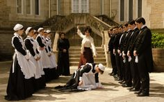 The staff from the Spanish TV series Grand Hotel in their uniforms .with their lovely owner