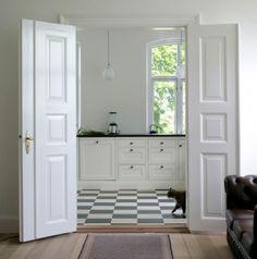 Gosto muito de piso preto-e-branco. E de gatos. E de janelões dando para o verde. E de portas duplas brancas com almofadas.... Gostei de quase tudo nesta cozinha....