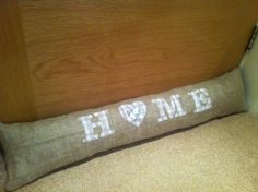 Hand made hessian draft excluder with word 'Home' appliqued onto it. The heart has mother of pearl buttons sewn into the centre. Draft Excluder, Door Draught Excluder, Door Draft, Hessian, Mother Of Pearl Buttons, Sewing A Button, Bamboo Cutting Board, Centre, Heart