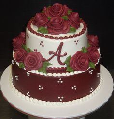 Two tier burgundy and white iced cake, with burgundy roses and initial.