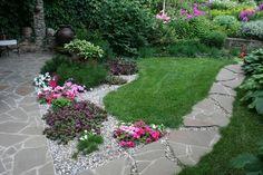 Petunien und lila blühende Bodendecker Pflanze im Kiesbeet