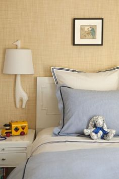 A giraffe sconce and grasscloth-covered walls are perfect in this bedroom by Elizabeth Dinkel.